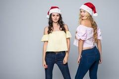 两个可爱的少妇画象圣诞节帽子的被隔绝在红色背景 免版税图库摄影