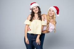 两个可爱的少妇画象圣诞节帽子的被隔绝在红色背景 库存图片