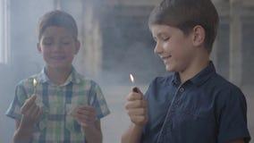 两个可爱的男孩在一间发烟性被放弃的屋子 有一次灼烧的比赛的,第二一个男孩与一个灼烧的打火机 影视素材