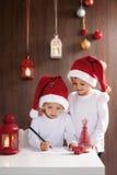 两个可爱的男孩,写信给圣诞老人 免版税库存图片