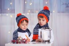 两个可爱的男孩,写信给圣诞老人 库存图片