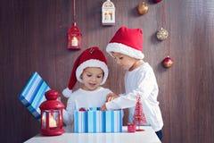 两个可爱的男孩,在圣诞节的打开的礼物 免版税库存图片