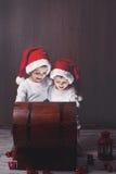 两个可爱的男孩,打开的木胸口,发光的光 图库摄影