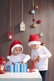 两个可爱的男孩,打开的礼物 免版税库存照片