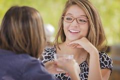 两个可爱的青少年的混合的族种女朋友谈话在饮料外面 免版税图库摄影