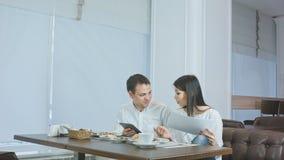 两个同事谈论工作,当吃午餐在咖啡馆时 免版税图库摄影