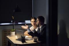 两个同事谈论新的项目在晚上会议 库存照片