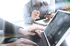 两个同事谈论网的设计师数据和数字式片剂 免版税图库摄影