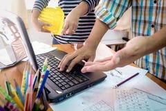 两个同事谈论运作的数据与建筑计划 免版税库存图片