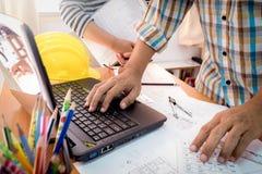 两个同事谈论运作的数据与建筑计划 免版税库存照片