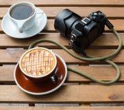 两个咖啡杯和一台照相机在木桌上 免版税库存图片