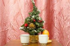 两个咖啡杯在一棵小人为圣诞树附近站立 库存照片