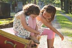 两个哀伤的女孩在公墓 免版税库存图片