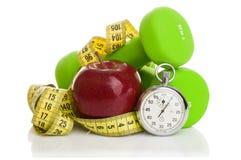 两个哑铃,红色苹果,测量的磁带 免版税库存照片