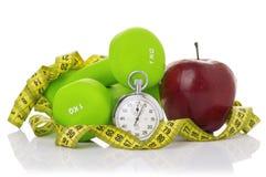 两个哑铃,红色苹果,测量的磁带 免版税图库摄影
