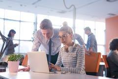 两个商人与膝上型计算机一起使用在办公室 免版税库存图片
