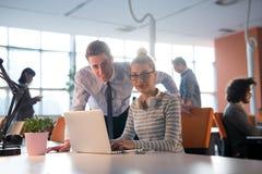 两个商人与膝上型计算机一起使用在办公室 库存图片