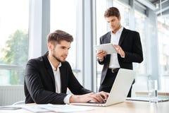 两个商人与膝上型计算机和片剂一起使用在办公室 库存照片