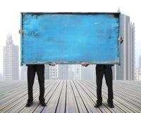 两个商人举行老蓝色空的木noticeboard 免版税图库摄影