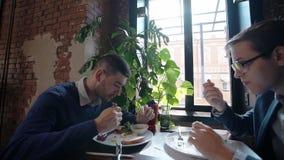 两个商人吃早餐在咖啡馆在研究论文以后一起报告 股票录像