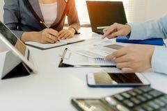 两个商人同事谈论在办公室桌上的计划财政图表数据与膝上型计算机和数字式片剂 概念事务a 免版税图库摄影
