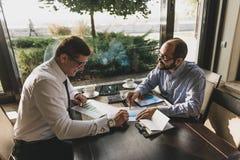 两个商人在一次会议上在咖啡馆 免版税库存照片