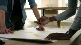 两个商人在业务会议指向与黄色纸的桌对此与铅笔 他们是 股票录像