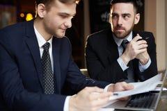 两个商人在会议的回顾文件 免版税图库摄影