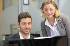 两个商人在办公室,研究计算机 免版税库存图片