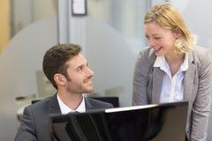 两个商人在办公室,研究计算机 免版税库存照片