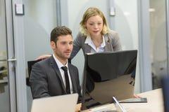 两个商人在办公室,研究计算机 免版税图库摄影