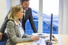 两个商人在办公室,研究计算机 图库摄影