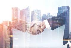 两个商人在城市握手 免版税图库摄影