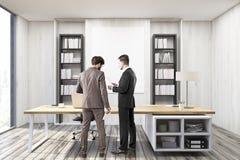 两个商人在有灰色墙壁的CEO办公室 免版税库存图片