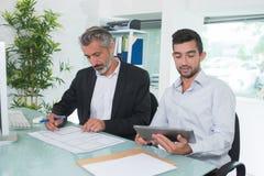 两个商人坐了在书桌一举行的片剂 免版税库存照片