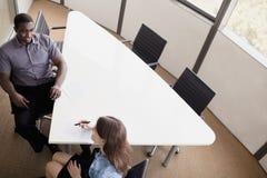 两个商人坐在会议桌上和谈论在业务会议期间 库存照片