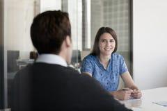 两个商人坐在会议桌上和谈论在业务会议期间 库存图片