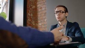 两个商人坐在咖啡馆和谈话在吃期间午餐 股票录像