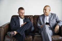 两个商人坐长沙发 图库摄影