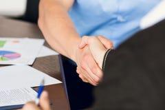 两个商人握手在秘书背景的  免版税库存图片