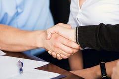 两个商人握手在w的秘书背景的  库存图片