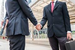 两个商人握手是与举行的不诚实和欺诈 免版税库存照片