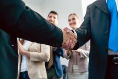 两个商人握手的特写镜头在一个重要协议以后的 免版税库存图片