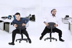 两个商人获得与椅子的乐趣在办公室 库存照片