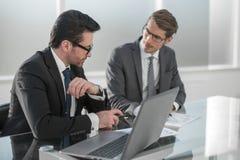 两个商人谈论在办公室在业务会议期间 图库摄影