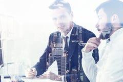 两个商人谈论材料在办公室,城市 库存图片