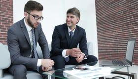 两个商人谈论财政文件 图库摄影