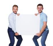两个商人运载并且显示空白的广告委员会,被隔绝 免版税图库摄影