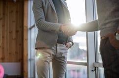两个商人震动手协议Coworking中心企业队工友在前面大全景窗口里站立 免版税库存图片
