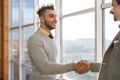 两个商人震动手协议Coworking中心企业队工友在前面大全景窗口里站立 库存图片